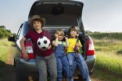 三孩子在汽车的后车箱坐自然 免版税库存照片