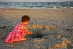 三岁使用与在一个凹陷的沙子的女孩在海滩 免版税图库摄影
