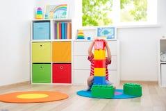 三岁儿童坐与立方体的地板 免版税图库摄影