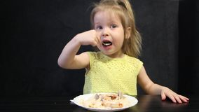 三岁的孩子吃煮熟的米和蘑菇与一把匙子在黑背景在黑桌上 影视素材