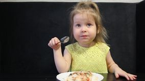 三岁的孩子吃煮熟的米和蘑菇与一把匙子在黑背景在黑桌上 股票视频