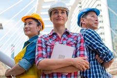 三工业工程师穿戴设计与胳膊的安全帽身分在大厦横渡了外面 免版税库存图片