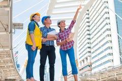 三工业工程师身分和看对右边穿戴与藏品检查和数字片剂的安全帽 免版税图库摄影
