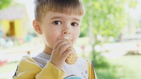 三年的一个小男孩吃着在奶蛋烘饼杯子的冰淇凌 影视素材