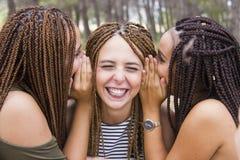 三年轻人和美女,当结辨的头发,采取selfie 图库摄影