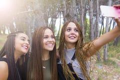 三年轻人和美女,当结辨的头发,采取selfie 免版税图库摄影