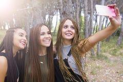 三年轻人和美女,当结辨的头发,采取selfie 免版税库存照片