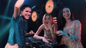 三微笑的少女结合演奏在转盘的音乐和唱歌曲 有转盘的Dj和白肤金发的歌手 股票录像