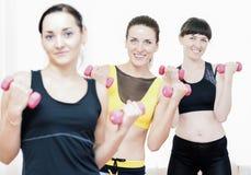 三愉快和行使与杠铃的微笑的白种人体育妇女 免版税库存图片