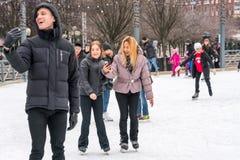 三愉快的青年人、妇女和人 使用MOBIL,当滑冰在公开冰s时,打电话 免版税库存图片