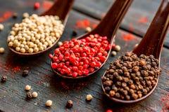 三把匙子用黑,桃红色和白色干胡椒 库存照片