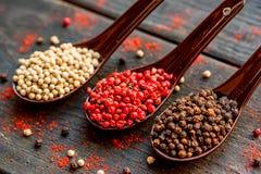 三把匙子用黑,桃红色和白色干胡椒 图库摄影
