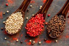 三把匙子用黑,桃红色和白色干胡椒 免版税库存照片