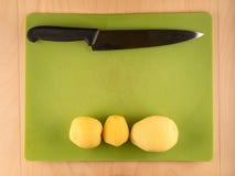 三把土豆和刀子在绿色塑料委员会 免版税库存照片
