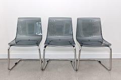 三把塑料椅子对墙壁 库存图片