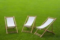 三把折叠椅在一个绿色公园 库存照片