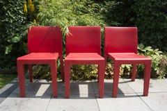 三把红色椅子在庭院里 免版税库存照片