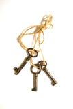 三把老钥匙栓与在白色背景的一条绳索 免版税库存图片