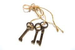 三把老钥匙栓与在白色背景的一条绳索 库存图片