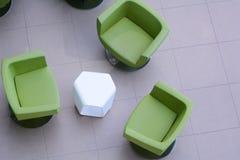 三把绿色扶手椅子顶视图有一张白色桌的 图库摄影