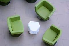 三把绿色扶手椅子顶视图有一张白色桌的 免版税库存图片