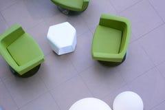 三把绿色扶手椅子顶视图有一张白色桌的 库存图片