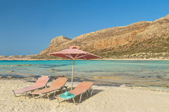 三把sunbeds、帽子和伞在海滩 图库摄影