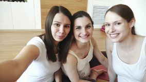 三摆在健身房的愉快的女孩看在照相机和做一selfie 股票视频