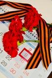 三支红色康乃馨包裹与在日历的乔治丝带与5月9日日期-胜利天静物画 库存图片