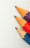 三支锋利的厚实的铅笔和被排行的纸 图库摄影