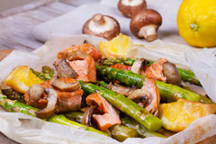 三文鱼、芦笋、蘑菇和柠檬在羊皮纸 免版税库存照片