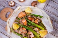 三文鱼、芦笋和蘑菇在羊皮纸 免版税图库摄影