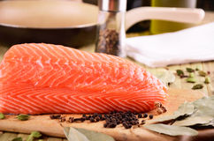 三文鱼内圆角和一个煎锅在桌上 免版税库存照片