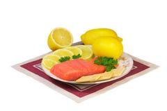 三文鱼内圆角和柠檬在一个盛肉盘在白色背景。 库存图片