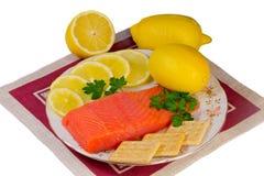 三文鱼内圆角和柠檬在一个盛肉盘在白色背景。 免版税库存图片