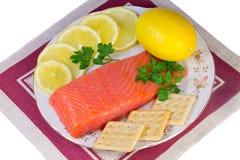 三文鱼内圆角和柠檬在一个盛肉盘在白色背景。 免版税图库摄影