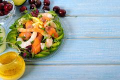 三文鱼和大虾与柑橘的夏天沙拉在蓝色木桌上调味 免版税库存照片