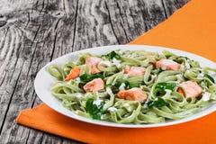 三文鱼和菠菜在白色盘的意大利细面条面团 图库摄影