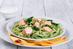 三文鱼和菠菜在白色盘的意大利细面条面团 免版税库存图片
