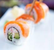 三文鱼寿司卷用鲕梨和黄瓜 免版税库存照片