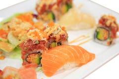 三文鱼寿司和辣金枪鱼卷在被隔绝的板材 图库摄影