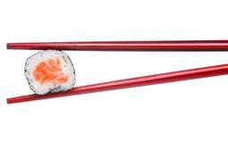 三文鱼寿司maki一和平在木红色筷子的 免版税图库摄影