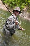 三文鱼快乐的渔夫抓住  库存图片