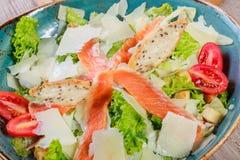 三文鱼沙拉用金枪鱼调味汁、帕尔马干酪、油煎方型小面包片、蕃茄、混杂的绿色、莴苣和杯在木背景的酒 库存照片