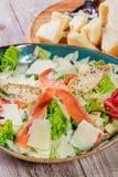 三文鱼沙拉用金枪鱼调味汁、帕尔马干酪、油煎方型小面包片、蕃茄、混杂的绿色、莴苣和杯在木背景的酒 免版税图库摄影