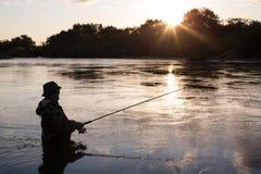 三文鱼渔夫抓住在日落的 免版税库存照片