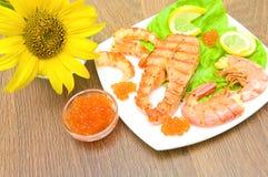三文鱼烤了牛排、烤虾和红色鱼子酱在木 库存照片