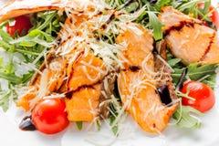 三文鱼片断、西红柿、莴苣、乳酪和调味汁新鲜的沙拉在白色板材关闭 库存图片