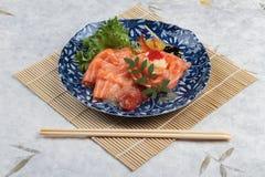 三文鱼生鱼片服务用石灰调味汁、土豆沙拉和ikura服务在有筷子的气喘的墨水板材在makisu膳食席子 库存照片