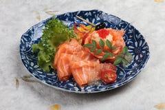 三文鱼生鱼片服务用石灰调味汁、土豆沙拉和ikura服务在washi日文报纸的气喘的墨水板材 免版税库存照片